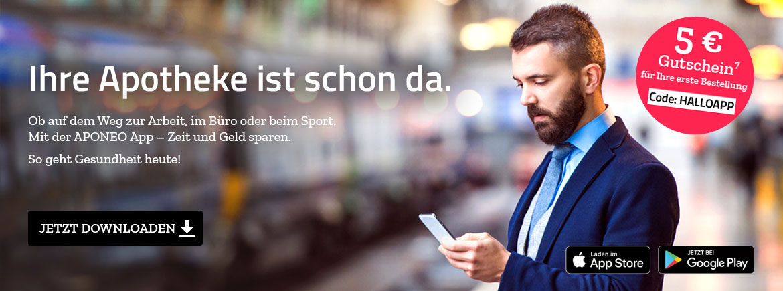 Mann im Anzug steht am Bahnhof und schaut auf sein Handy und Aponeo App